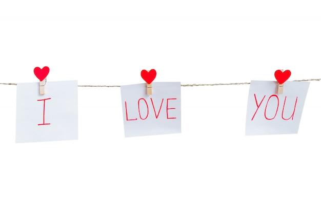 白い背景に分離された自然のコードに掛かっている赤いバレンタインの愛心ピン。紙に刻まれた碑文が大好きです。