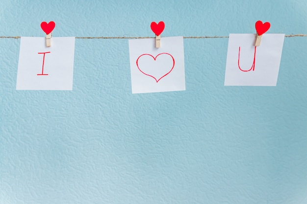 青い背景の自然なコードに掛かっている赤いバレンタインの愛心ピン。紙に刻まれた碑文が大好きです。