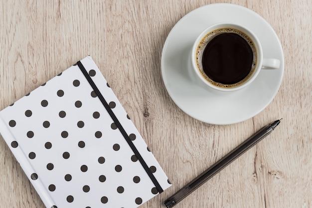 ビジネスおよびオフィスコンセプト-黒と白の水玉カバーノート、ペン、木製のテーブルにブラックコーヒーのカップ。上面図。