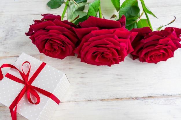 赤いリボンの弓と木製の背景に名園の赤いバラとベージュの水玉ギフトボックス。