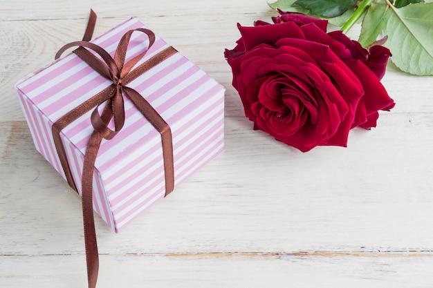 茶色のリボンの弓と木製の背景に名園の赤いバラと紫のストライプギフトボックス。休日のグリーティングカード。