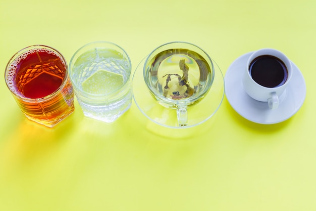 さまざまな飲み物-黄色の背景にコーヒー、炭酸水、リンゴジュース、緑茶を飲むのトップビュー。健康的な生活とダイエットのコンセプト