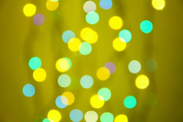 緑、オレンジ、黄色の背景に抽象的なぼやけたライト