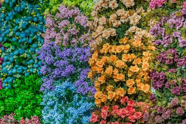 オレンジ、青、ピンク色の背景の人工の咲くバラ