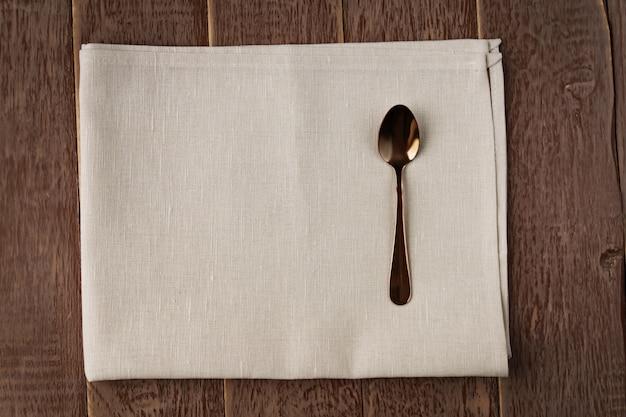 Взгляд сверху салфетки ткани бежевого цвета и, который служат ложки чая на деревянном столе.