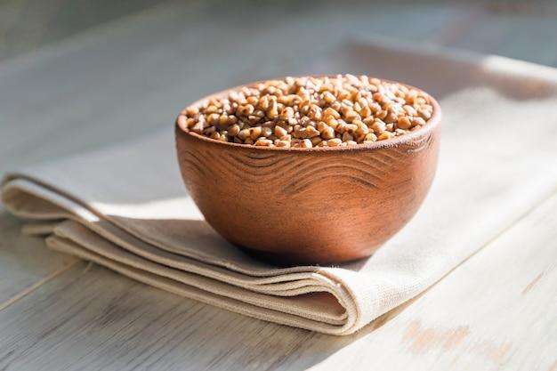 木製テーブルの上の茶色の粘土ボウルで乾燥そば。健康的な食事のためのグルテンフリー穀物