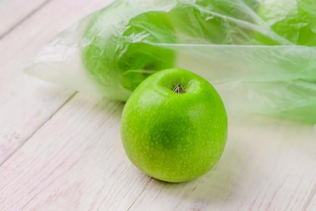 木製のテーブルのビニール袋に新鮮な青リンゴ。プラスチックの非生態的使用の環境概念