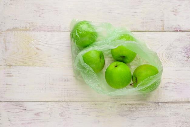 Свежие зеленые яблоки в полиэтиленовом пакете на деревянном столе. экологическая концепция неэкологического использования пластика