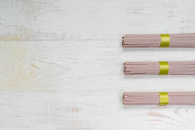 書いてみます木製のテーブルに生そば。伝統的な日本食。トップビュー、コピースペース