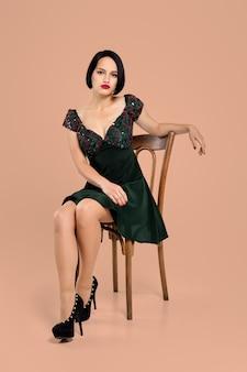 ベージュのスタジオの椅子に座っているショートドレスのゴージャスな女性