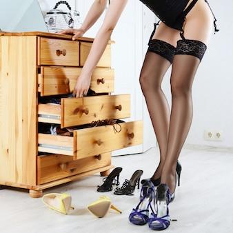 引き出しの中にランジェリーを選ぶ女性、床に点在する複数の靴