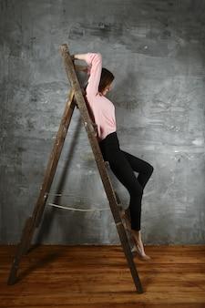 Мечтательная девушка сидит на лестнице в профиле