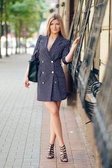 Красивая девушка в пиджаке-платье гуляя по улице