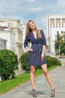 Красивая девушка в пиджаке-платье гуляя по улице в жаркий летний день