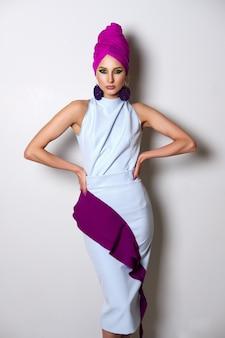 フィットドレスとターバンの頭の上の美しいファッションモデルの肖像画。明るいメイクと大きなイヤリング