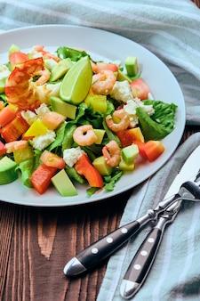 Салат с авокадо, сыром фета и креветками на старом деревянном столе