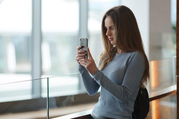 Красивая женщина с рюкзаком на балконе, делая фото с ее смартфон через окно