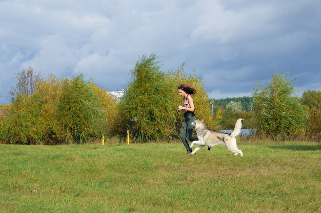 都市公園におけるハスキー犬と遊ぶ少女。犬とジョギング。