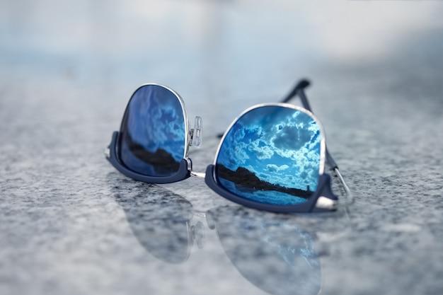 ガラスの青い空の反射とサングラス。セレクティブフォーカス写真。