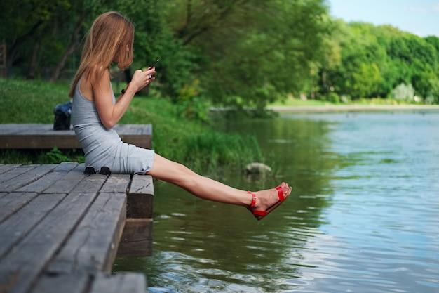 川の土手とメッセージングの木製の桟橋に座っている女の子の側面図。風に吹かれて髪の美しい女性。
