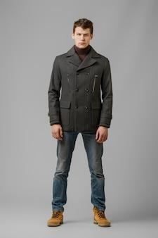 Полная длина портрет красавец в теплое пальто, позирует в студии