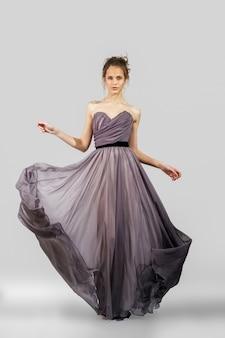 イブニングドレスでポーズ美しい少女。ファッションモデルの完全な長さの肖像画。
