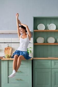 台所のテーブルの上に座って自分自身を伸ばして幸せな女の子