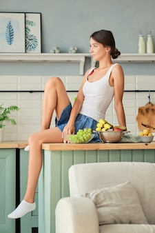 新鮮な果物とテーブルの上のキッチンに座っているかわいい女の子