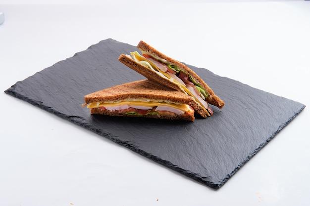 ハム、チェダーチーズ、キャベツ、白で隔離されるトマトのクラブサンドイッチ