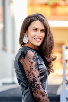レースの袖が屋外にある短い革のドレスの魅力的な女性