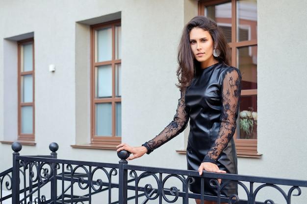 階段を降りて短い革のドレスで魅惑的な女性