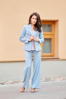 路上でスカイブルーのパンツスーツで美しい女性