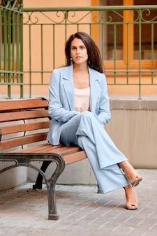 Стильная женщина в небесно-голубом брючном костюме отдыхает на скамейке возле офиса