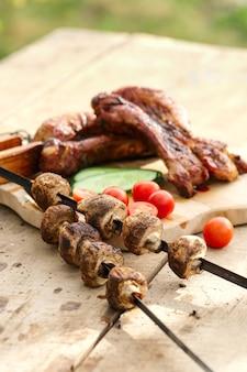 Жареные ребрышки и шампиньоны на шампуре со свежим огурцом и помидорами на деревянном столе на открытом воздухе