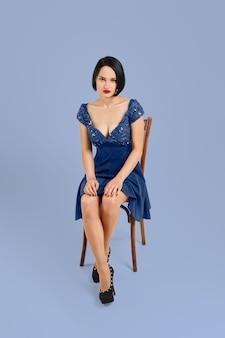 Красивая девушка сидит на стуле, держа ладони на коленях