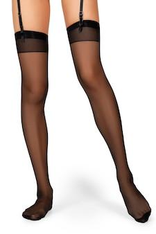白で隔離されるガーターと黒の縫い目ストッキングでスリムな女性の足