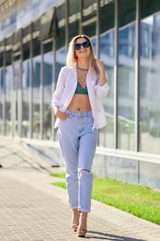 ビジネスセンターに沿って歩く白いシャツとボーイフレンドのジーンズの女性
