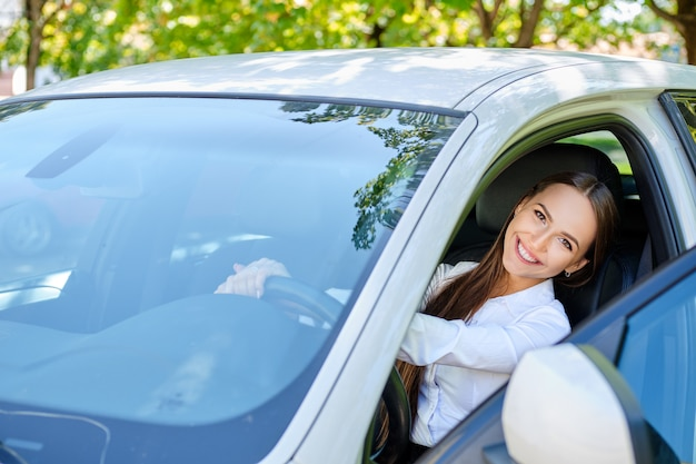 車のホイールの後ろに美しい笑顔ブルネットの少女