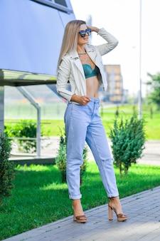 ブルージーンズと太陽を楽しむ白い革のジャケットのきれいな女性
