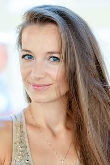 そばかすとないメイクアップを持つ若い女性のクローズアップの肖像画
