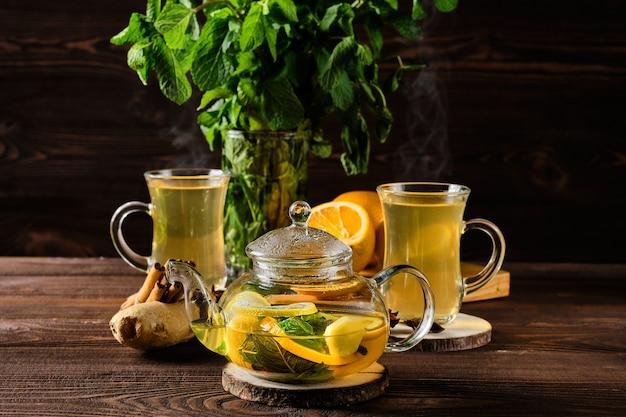 朝の素朴な木製のテーブルにレモン、オレンジ、ジンジャー、ミントと熱いお茶