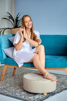 Красивая девушка держит крем для ног в руках, сидя на диване в белом шелковом халате