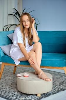 Красивая девушка, применяя крем для ног в домашних условиях, сидя на диване в белом шелковом халате