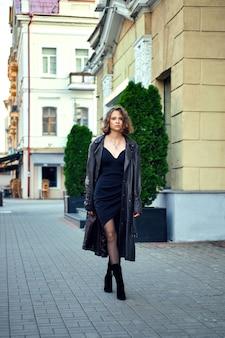 イブニングドレスと広いオープンメンズ革マントの女性が通りを歩いて