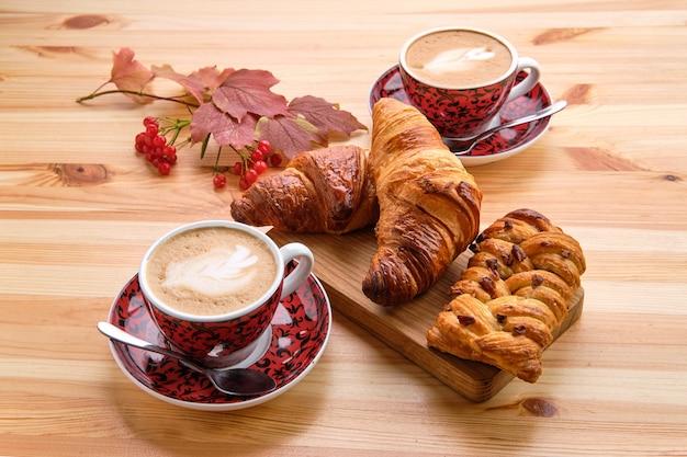 Булочка с изюмом из слоеного теста и хрустящий круассан на деревянном столе с кофе