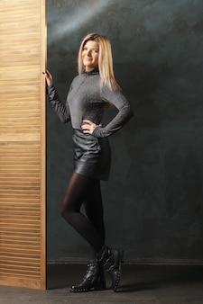 トップ、革のズボン、密集したタイツで屏風の近くでポーズかわいい女の子