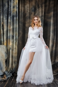 短いウェディングドレスの美しい花嫁の完全な長さのスタジオポートレート