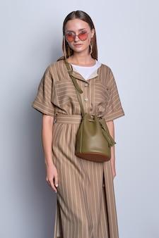 Модная леди в больших очках в полосатом оливковом платье с кожаной сумочкой позирует на сером