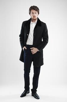 Брутальный красивый небритый мужчина с бородой и усами в бархатном пальто с меховым воротником