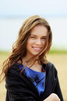 Улыбающаяся симпатичная девушка на пляже в ветреный день с шерстяной пленкой на плечах